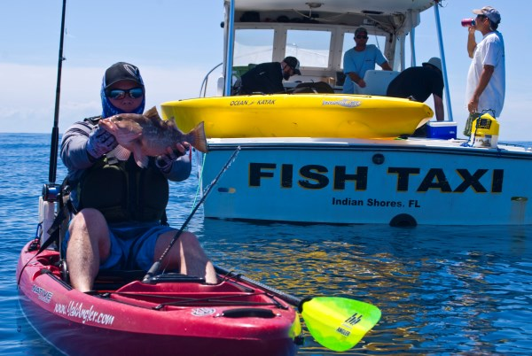 mark with a red grouper caught kayak fishing