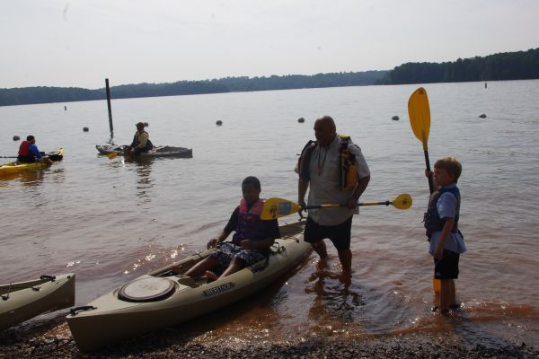 After PFD and paddle fitting and instruction, Tony gets kids in boats while the water marshalls stand by.